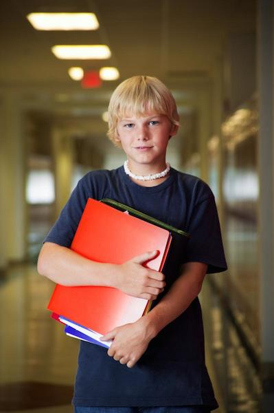 boy holding books in hallway